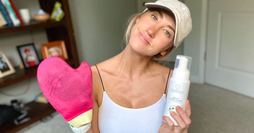 woman holding white bottle of self tanner and hot pink mitt