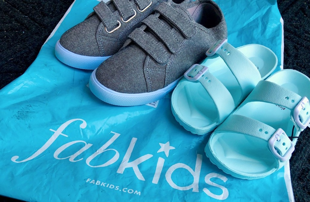 gray tennis shoes and blue sandals on blue fabkids bag