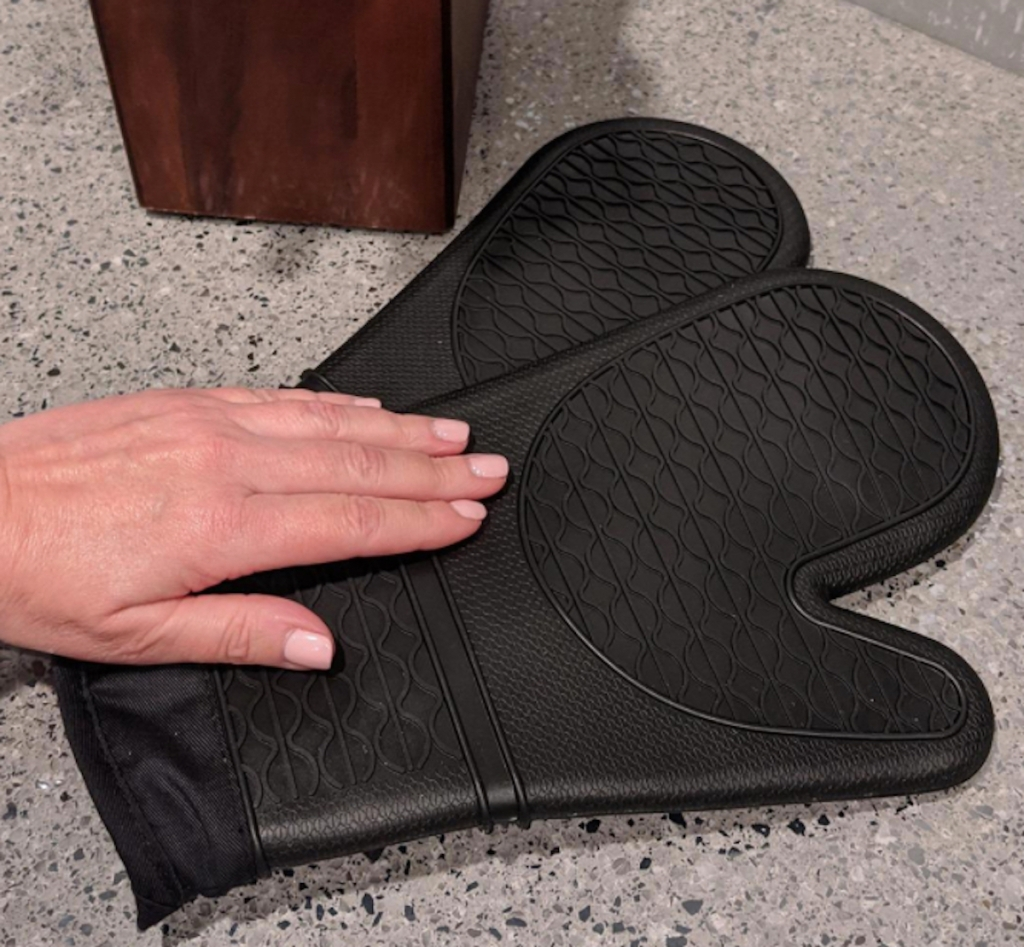 hand on black pair of silicone oven mitts