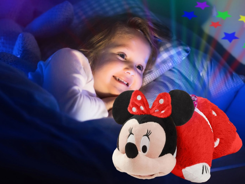 girl laying in bed with minnie pillow pet