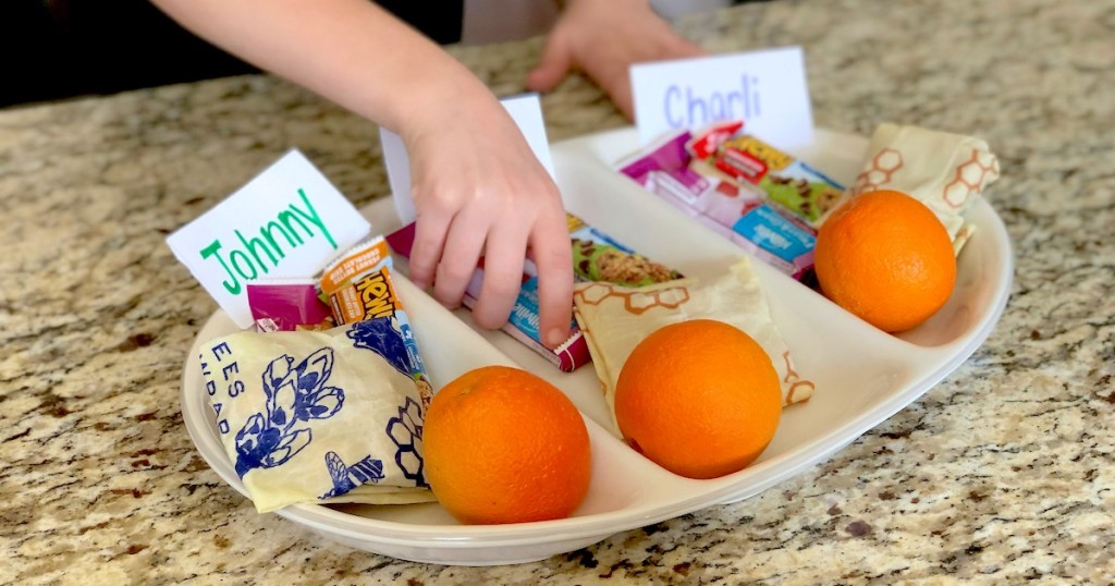 kids hand grabbing snack from snack tray with oranges bees wrapped food and snack bars