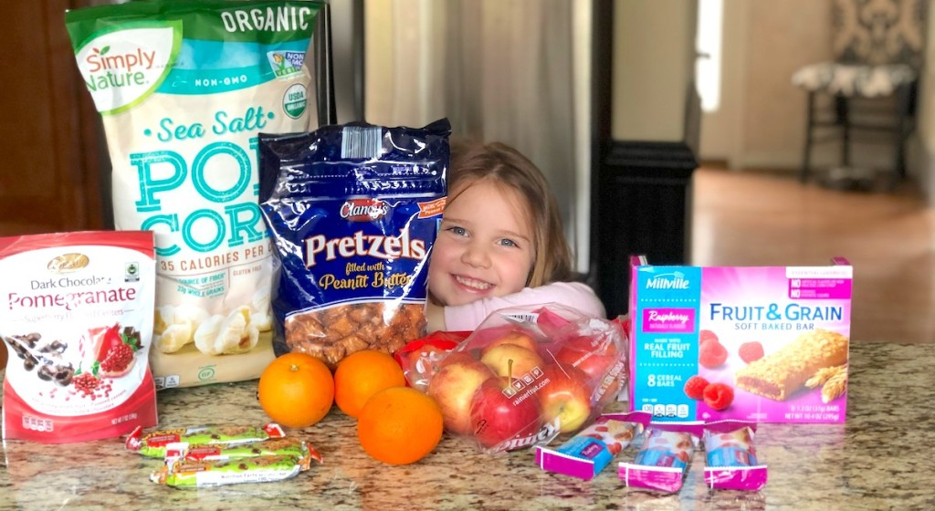 toddler girl smiling surrounded by tons of different snacks on counter