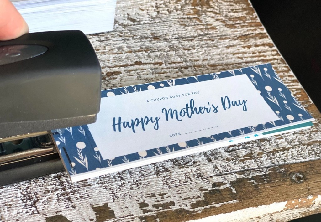 stapler putting together coupon book for mom