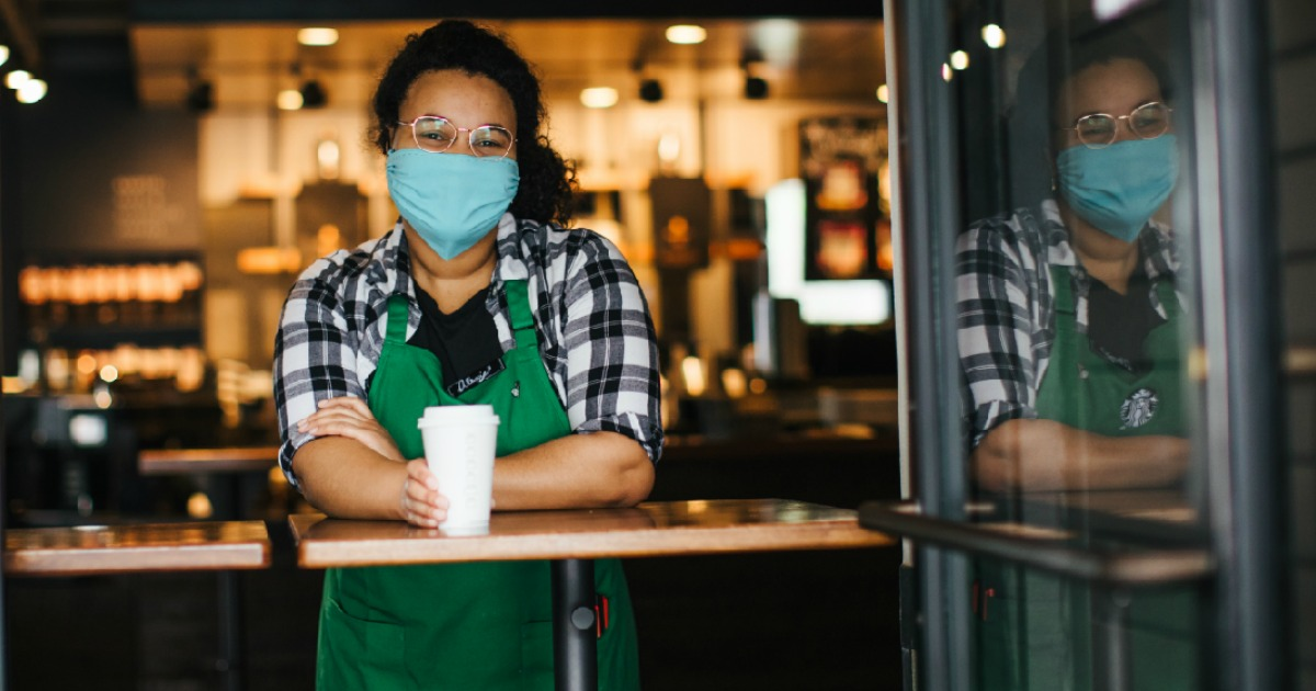 barista wearing health mask standing at counter