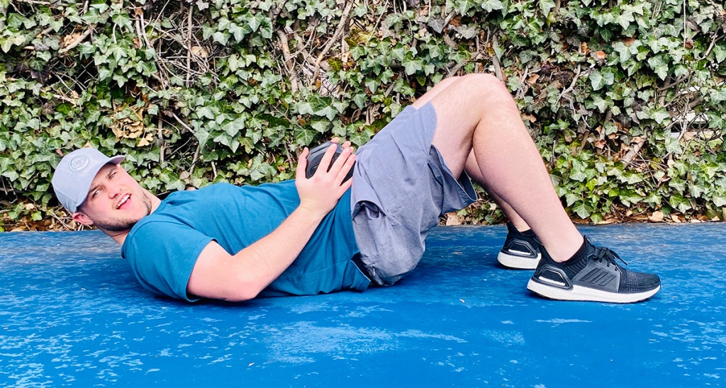 man laying on ground for glute bridge workout