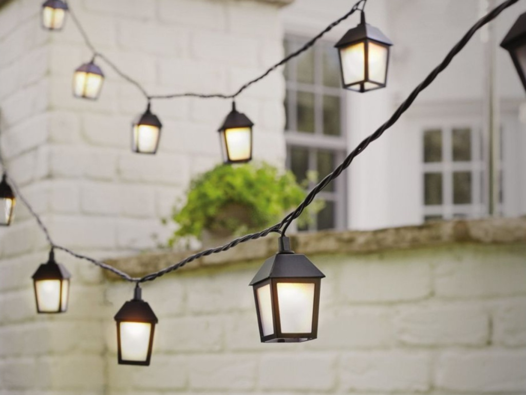 lantern lights hanging outdoors with white brick wall in background
