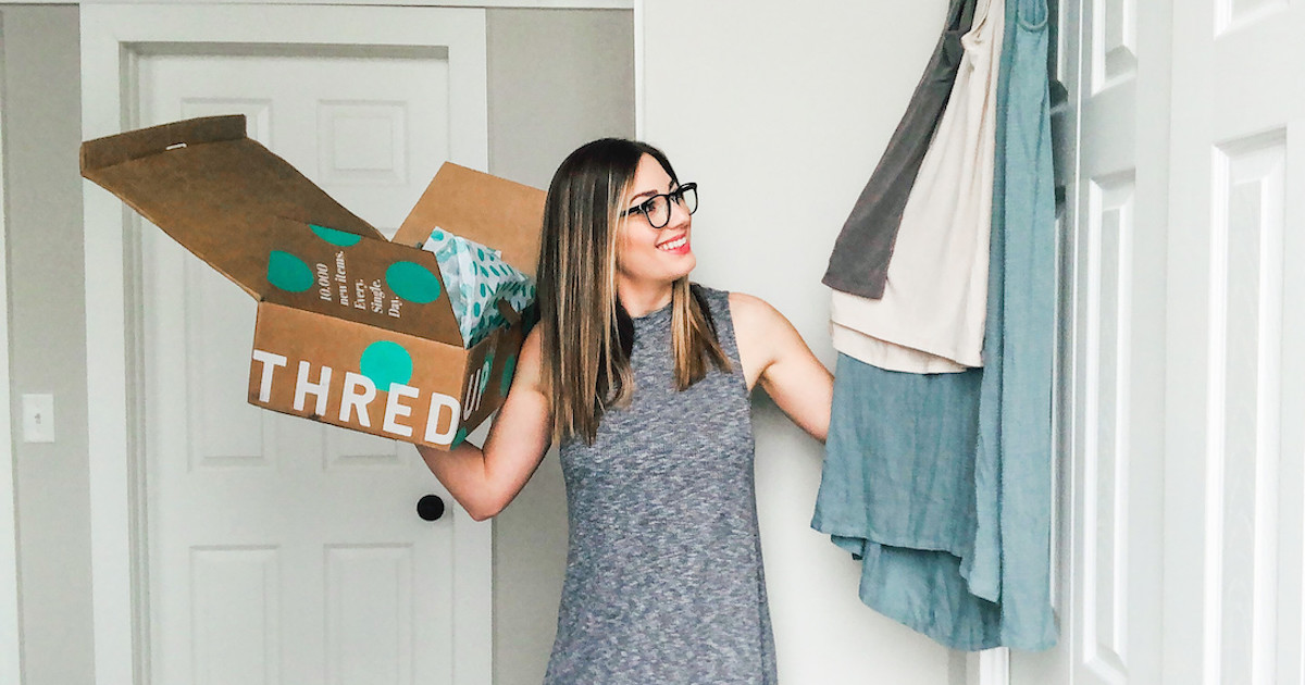 woman holding thredup box looking at clothes hanging up on door