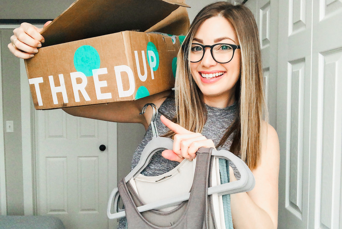 woman holding up a thredup box and holding clothes on hangers