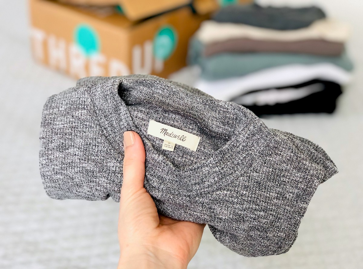 hand holding a gray madewell piece of clothing