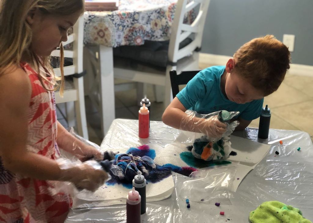 two kids at table tie dying shirts with various colors