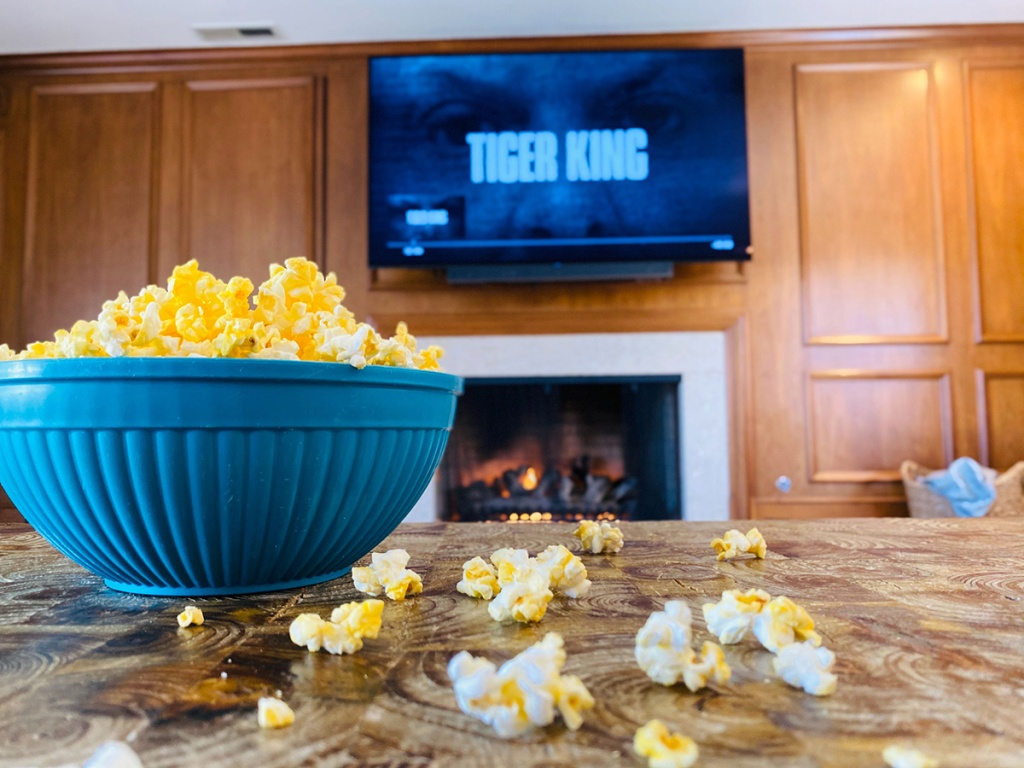 bowl of popcorn and tiger king title screen on tv