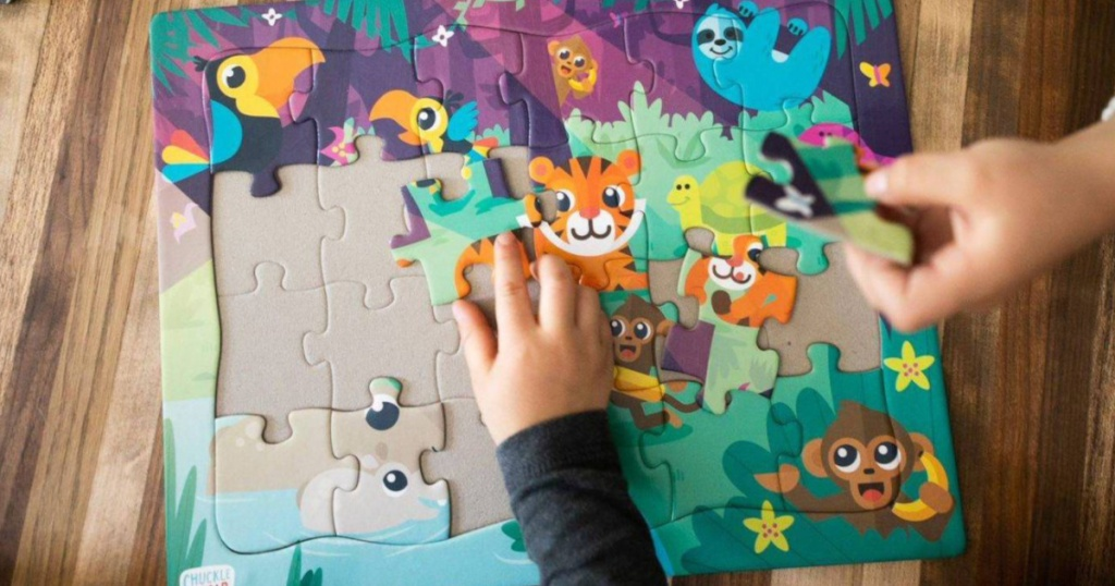 kids hand putting animal puzzle together