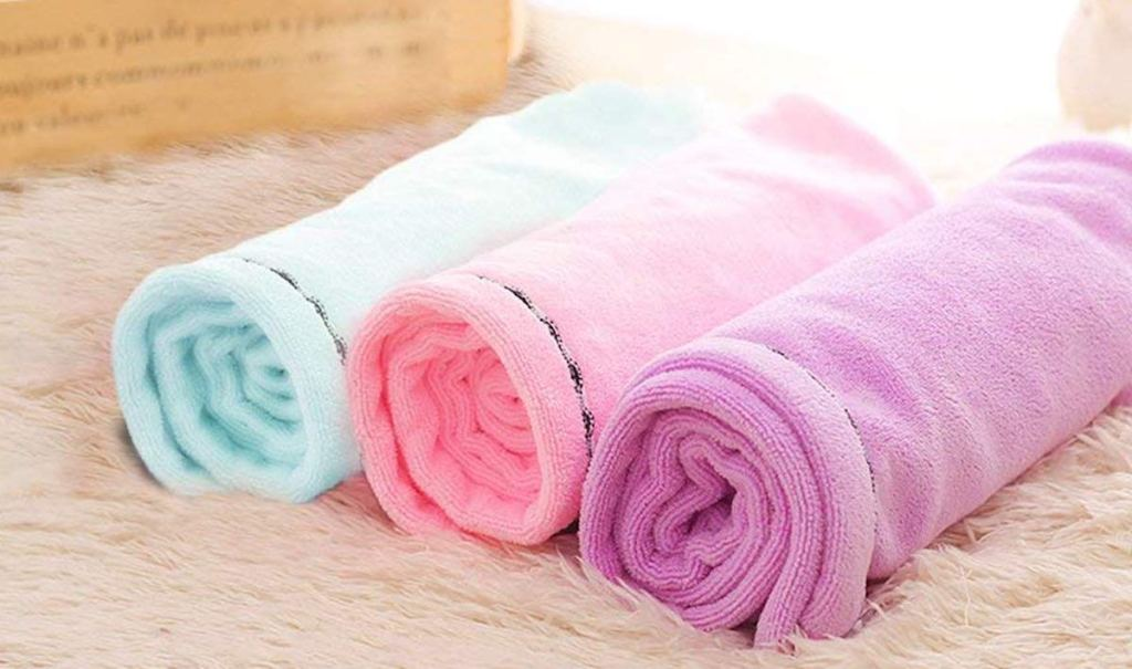 blue pink and purple towels rolled and laying on fur blanket