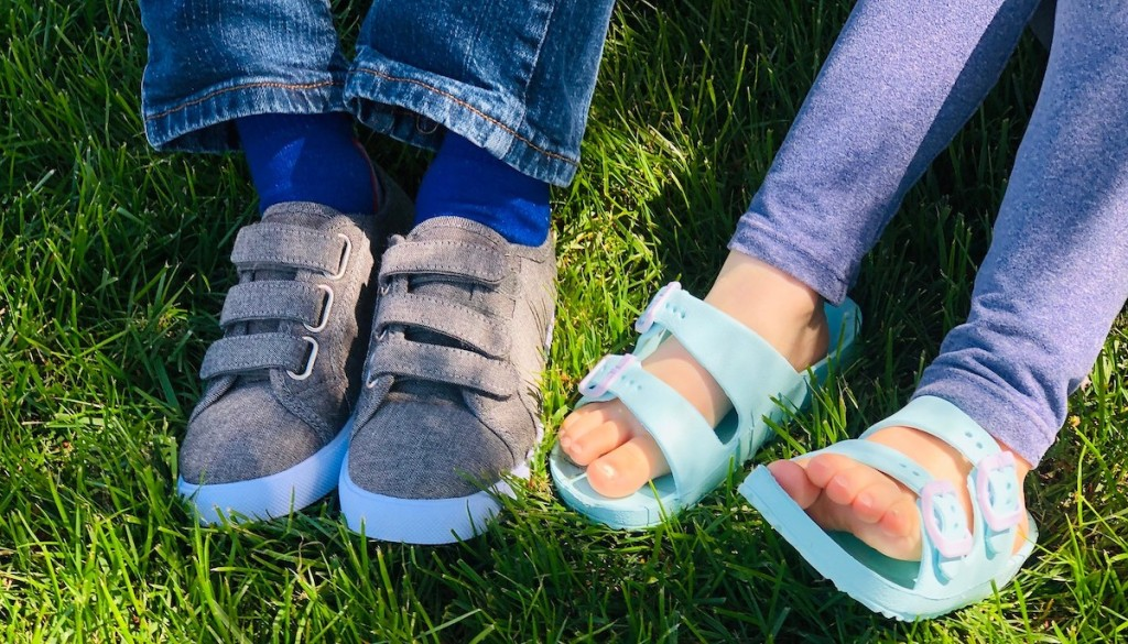Two kids wearing a pair of gray Velcro shoes and blue sandals