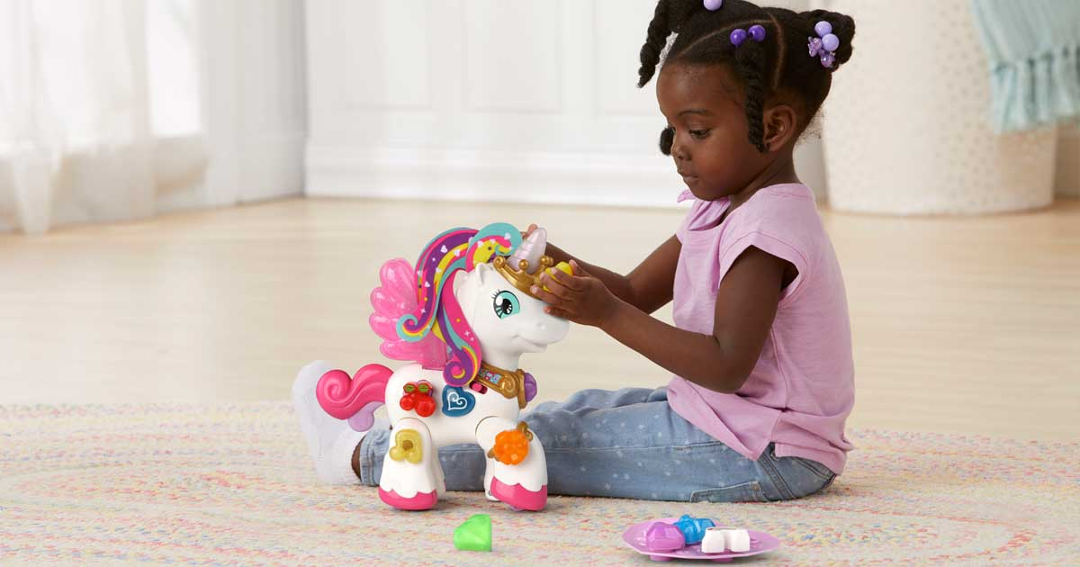 little girl playing on the floor with unicorn from vtech