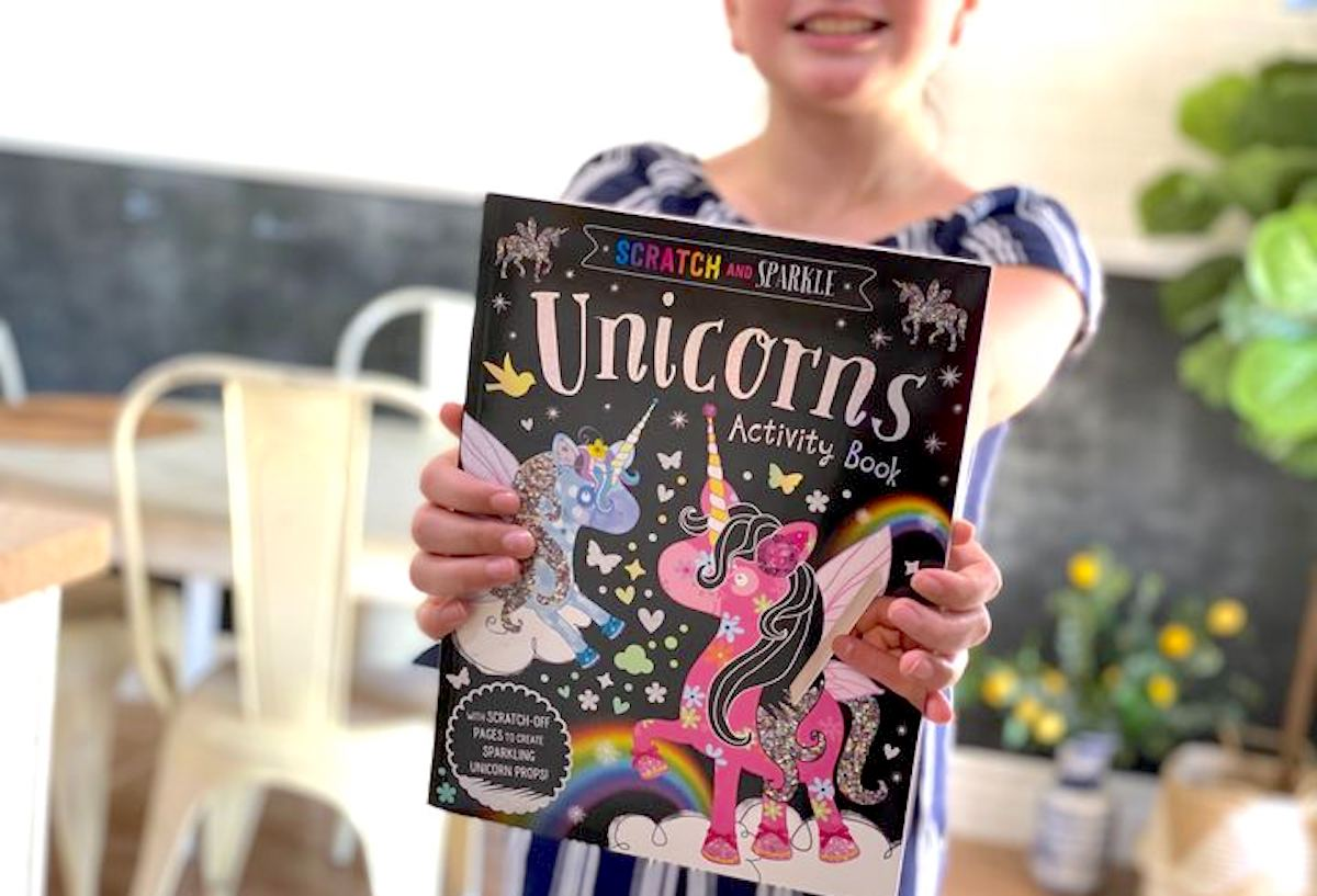 girl holding a unicorn activity book