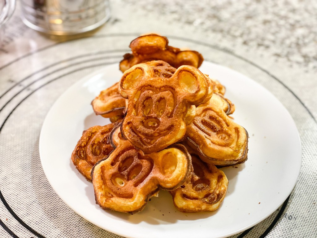 Tons of Mickey Mouse shaped waffles laying on white plates