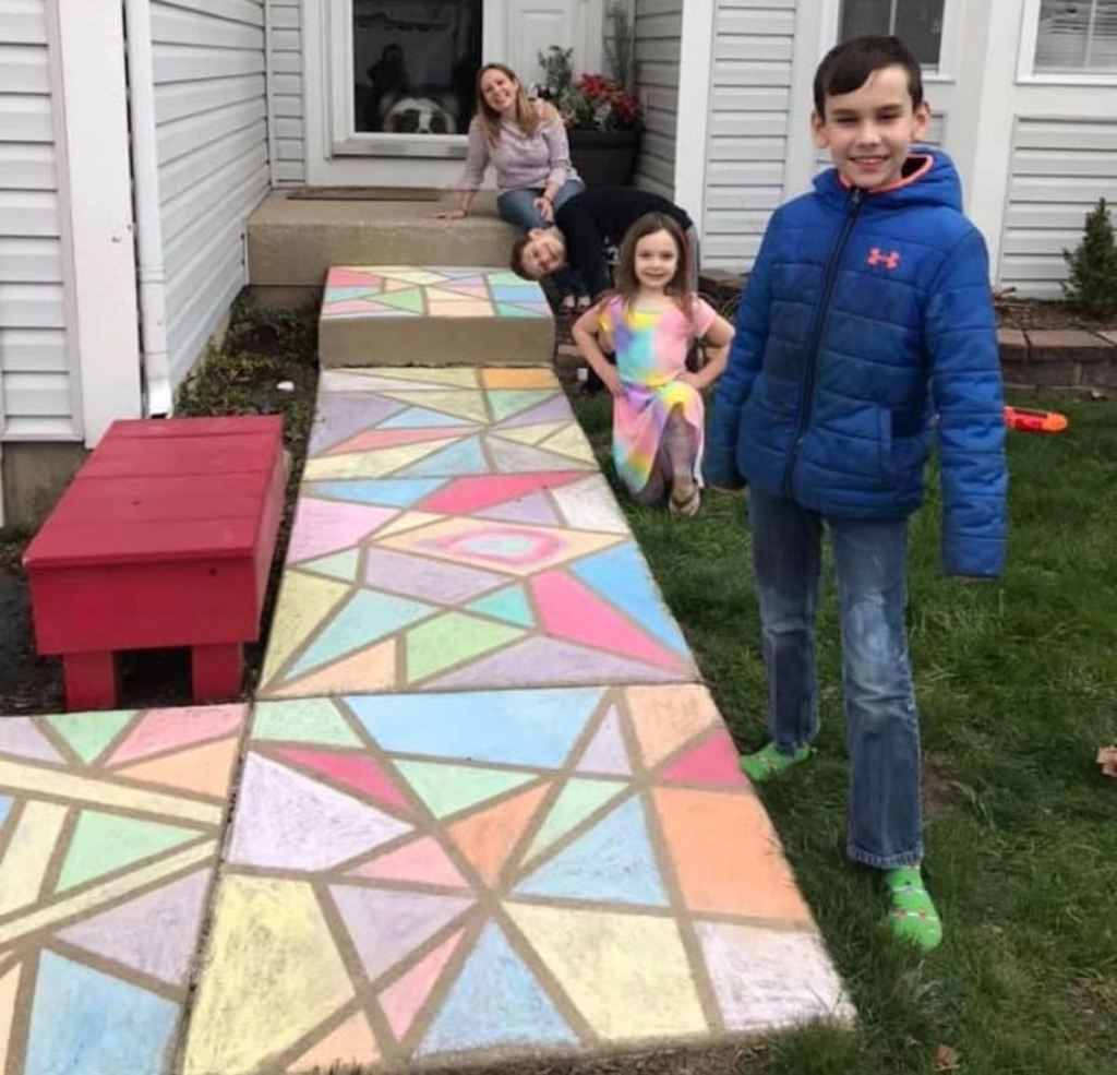 kids outside standing in front of colorful chalk art