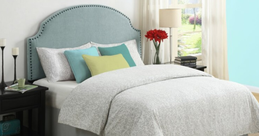 bed with brown furniture and blue nail head headboard with gray comforter and green throw pillows