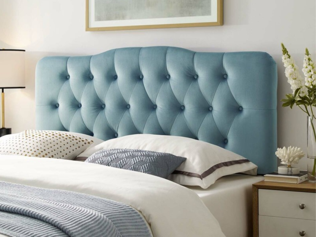 bed with white and blue bedding and throw pillows and blue tuffed headboard