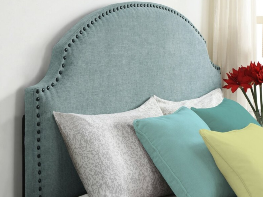 blue nail head headboard with white blue and yellow throw pillows