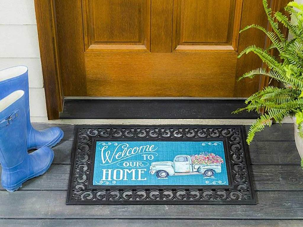 welcome to our home doormat with rain boots and a fern