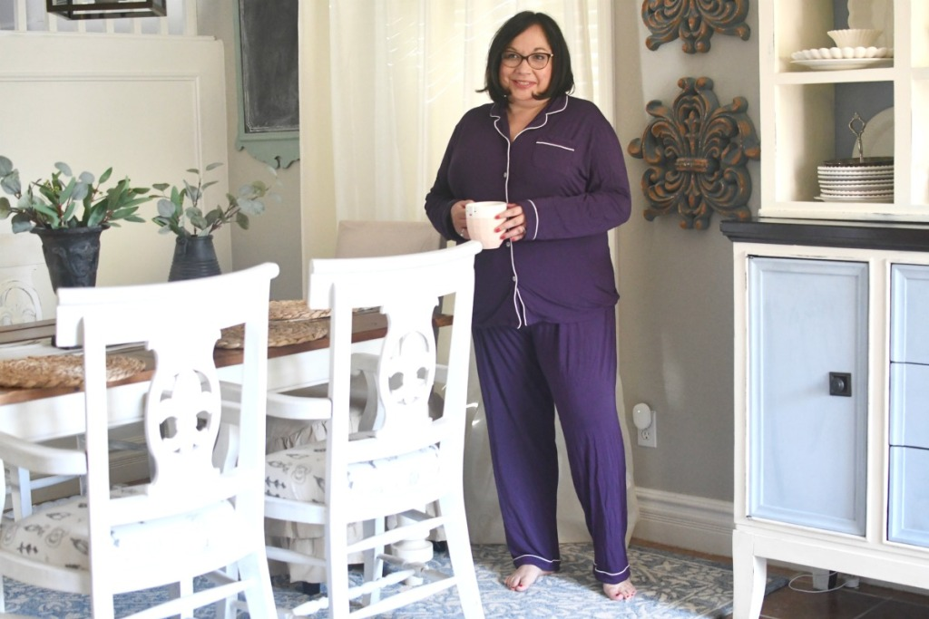 woman standing next to dining room table holding coffee mug