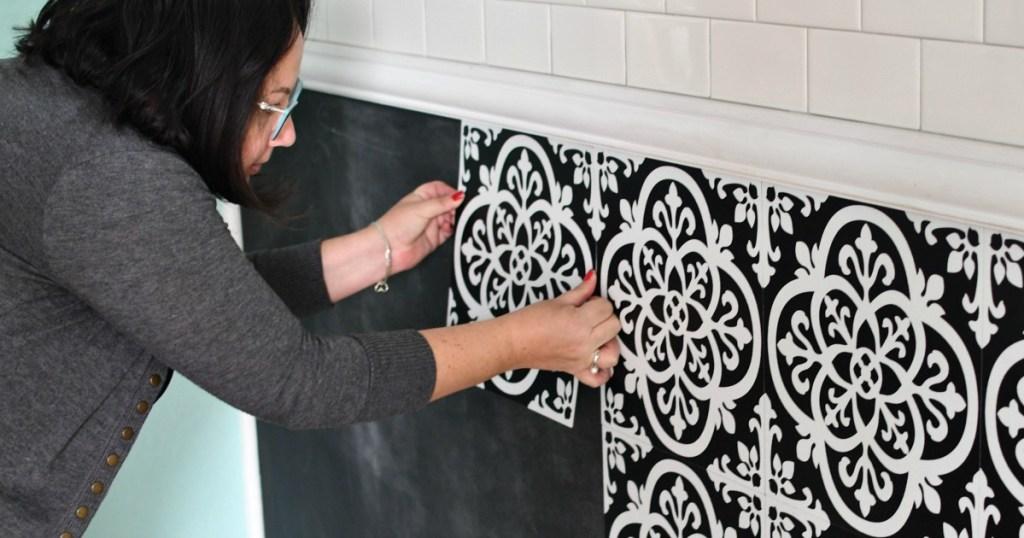 woman installing peel and stick floor pops tile