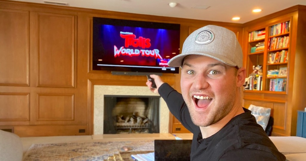 man with surprised happy face holding remote with trolls world tour on screen