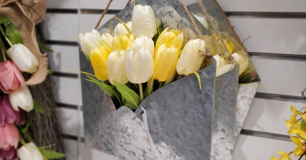 white and yellow tulips in hanging tin on store wall