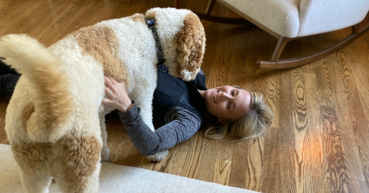 woman laying on floor with dog