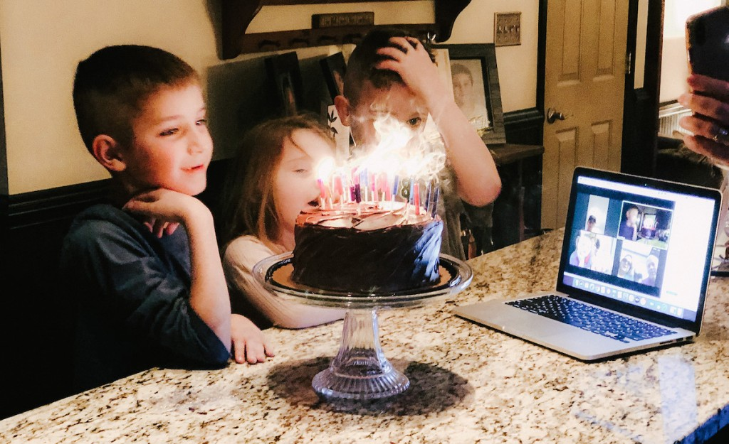 kids standing in front of cake with candles with computer on granite countertop