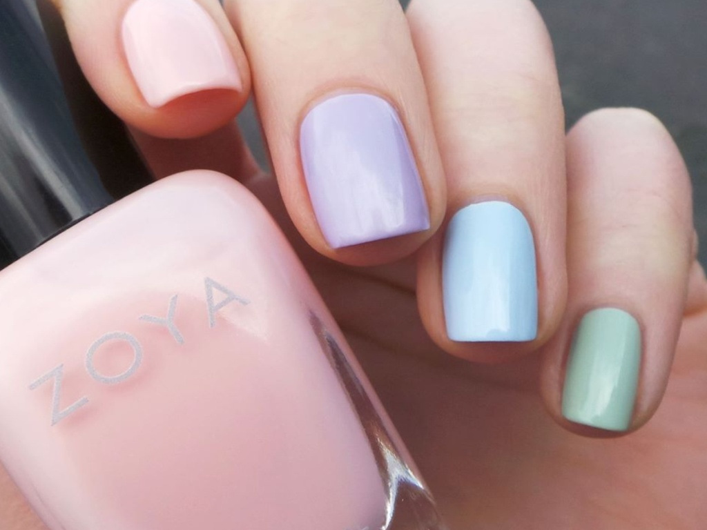 hand with colorful painted nails holding pink ZOYA nail polish
