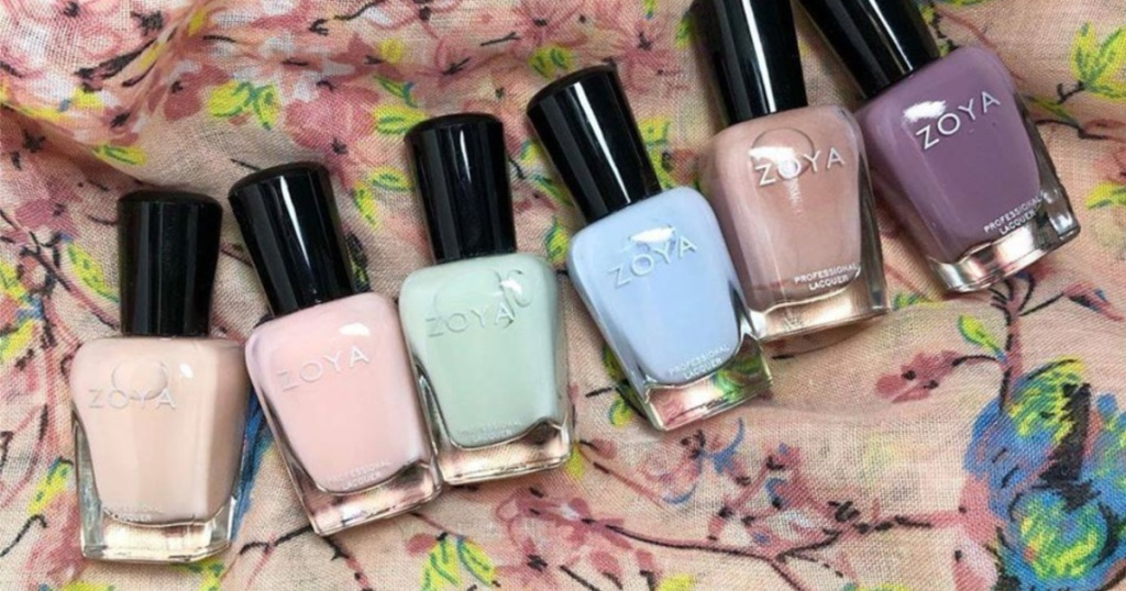 6 colorful ZOYA nail polishes laying on flower fabric