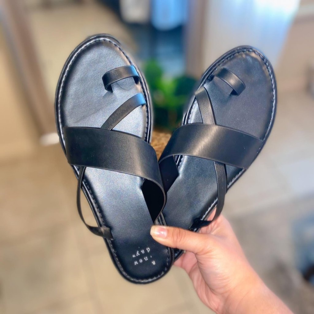 woman hand holding black pair of Women's Kallima Faux Leather Toe Ring Style Slide Sandals