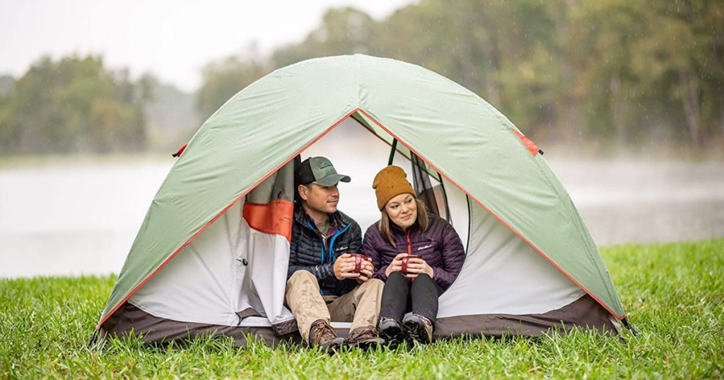 light grey tent with green rain shield with man and woman sitting inside door opening