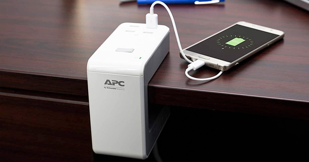 white u-shaped surge protector clipped on to edge of desk with phone plugged in and charing