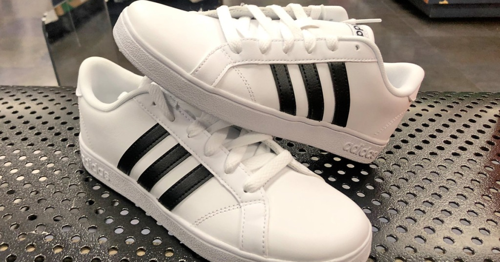 pair of white adidas sneakers with three black stripes on each side