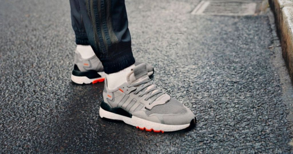 Adidas sneakers on mans feet standing on asphalt