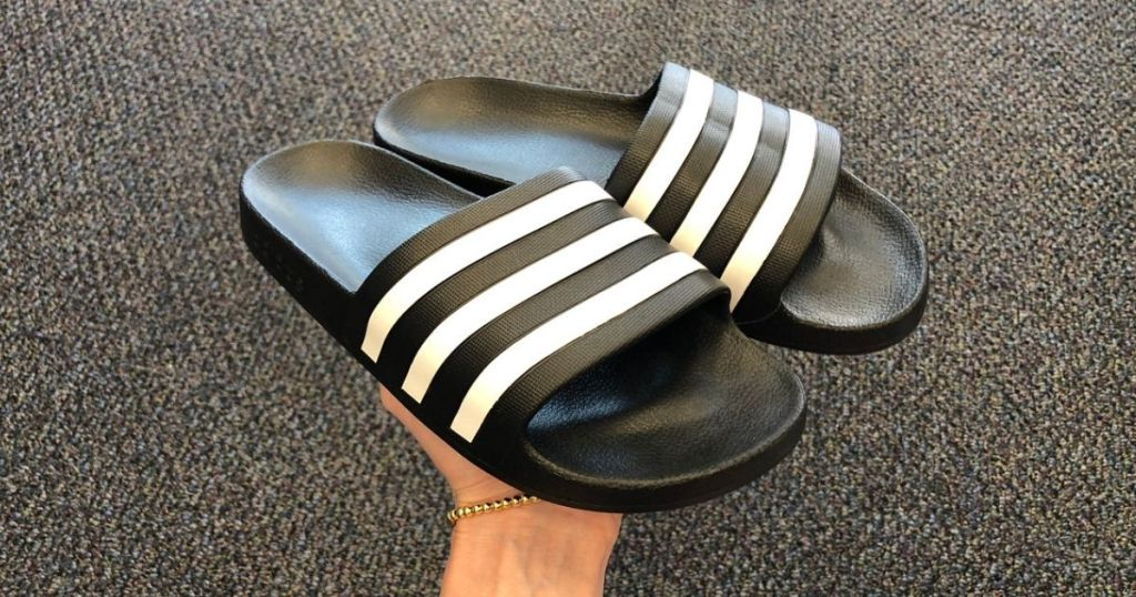 person holding a pair of black adidas slides with white stripes on top straps
