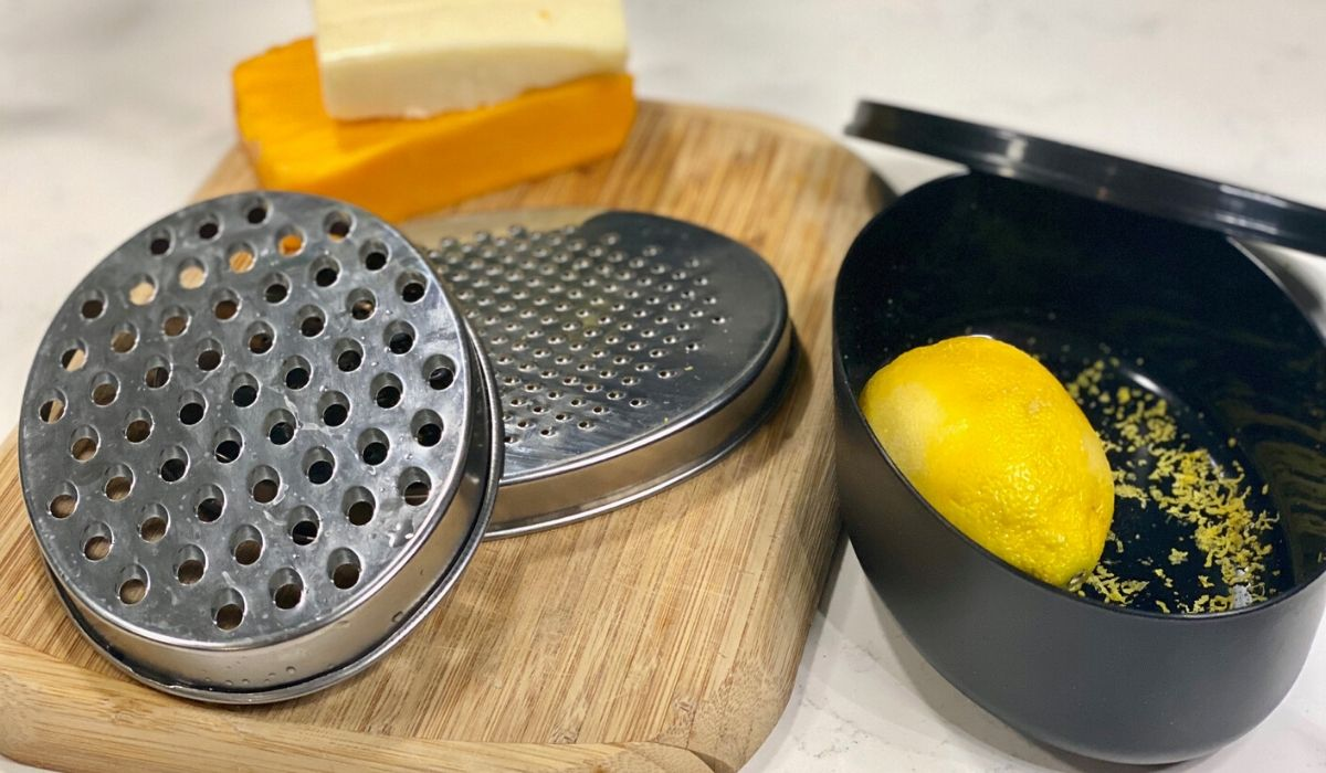 Amazon cheese grater and citrus zester with storage compartment sitting on the counter with a lemon and block cheese