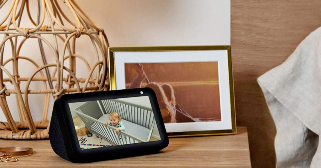 amazon echo show sitting on bedroom nightstand next to lamp and picture frame
