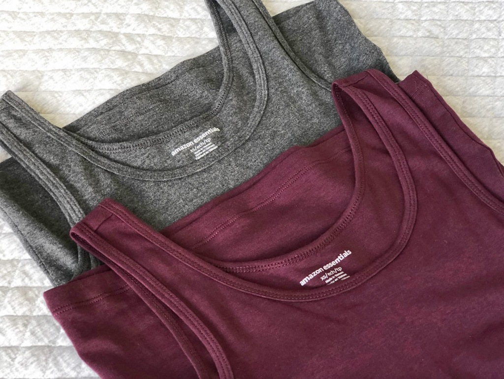 two amazon essentials brand tank tops in grey and maroon laying on bed