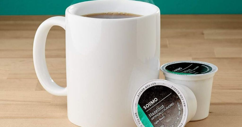 coffee cup with 2 k-cups next to it