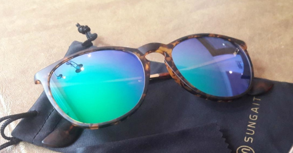 Women's reflective sunglasses on table top with black storage bag