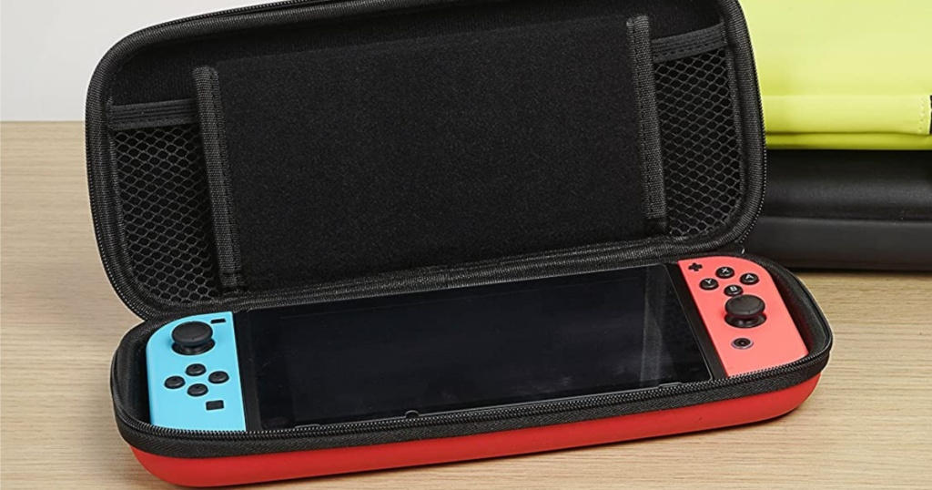handheld gaming console inside red and black carrying case on table with black case and yellow case