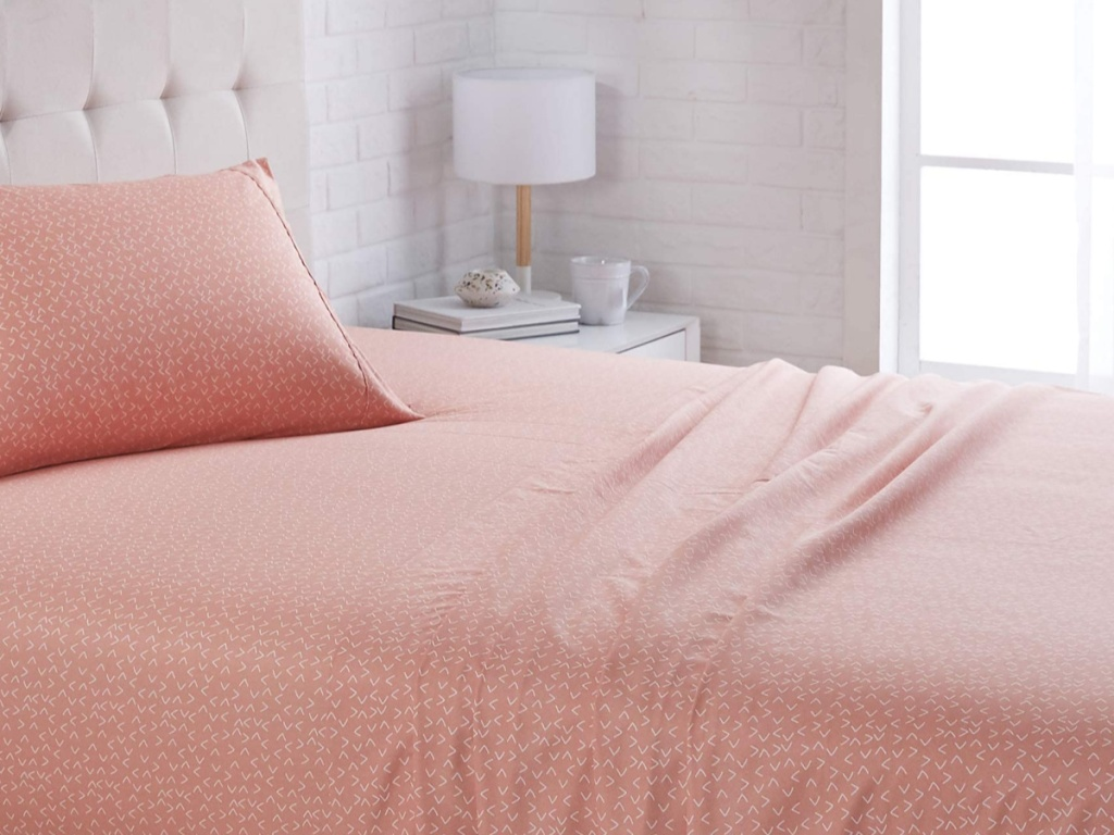 AmazonBasics Sheet Set on a bed next to a white table and lamp