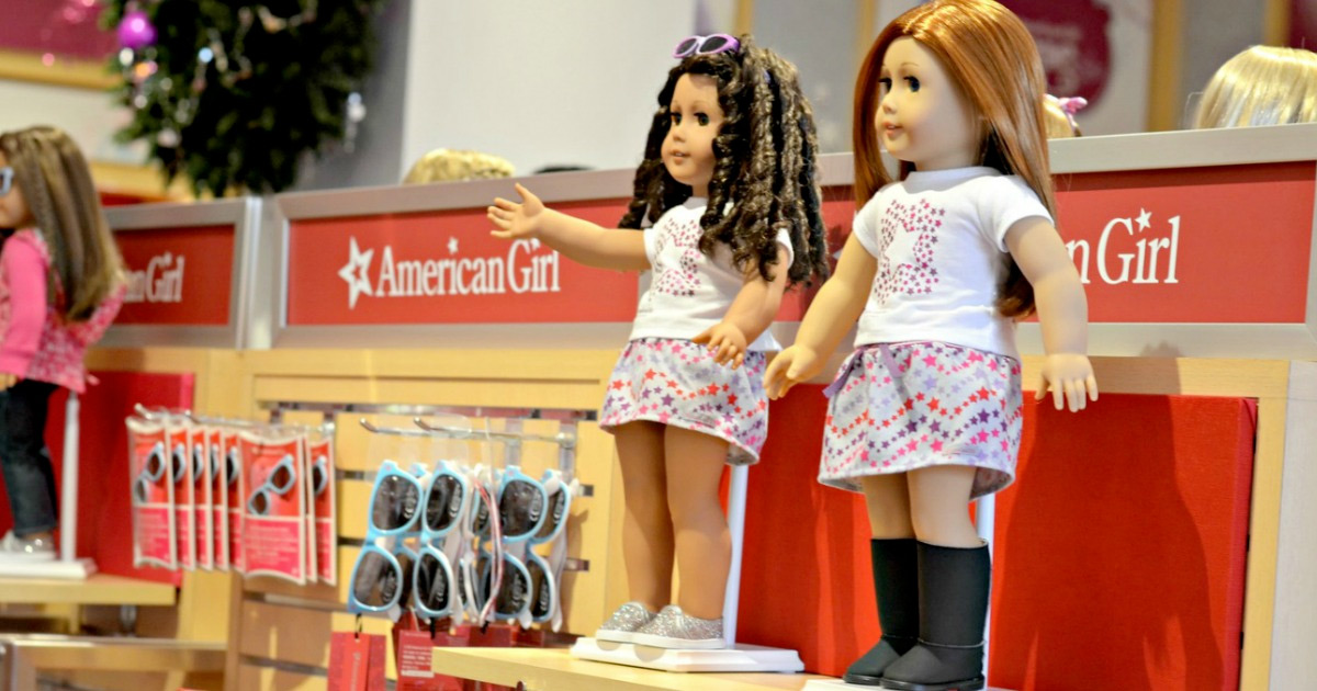two american girl dolls on store display shelf at american girl store