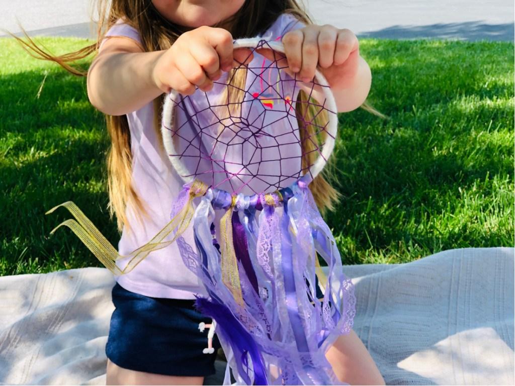 little girl holding craft