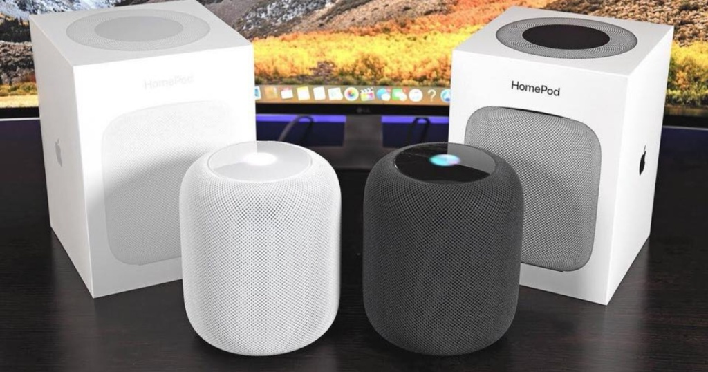 two white and space apple homepods out of the box with the boxes in the background